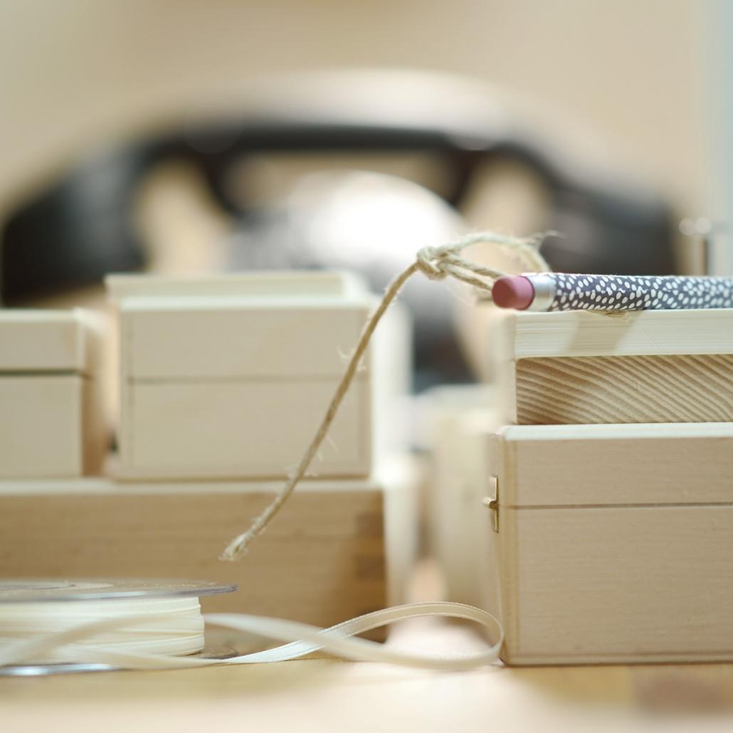 Schreibtisch im Atelier mit Holzboxen und nostalgischem Telefon