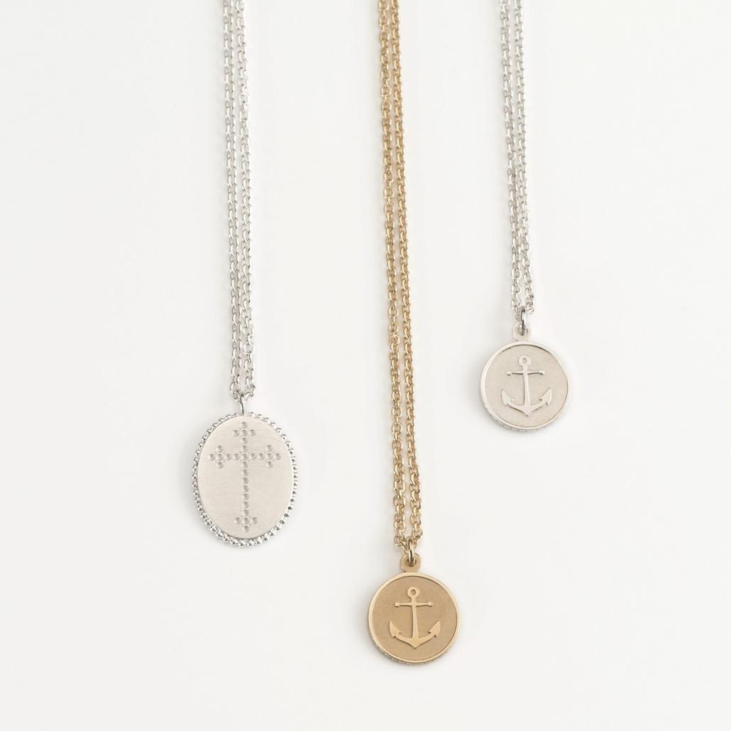 Drei 'Companion' Anhaenger: ein ovaler Kreuzanhaenger in Silber, zwei runde Ankeranhaenger in Gold und Silber